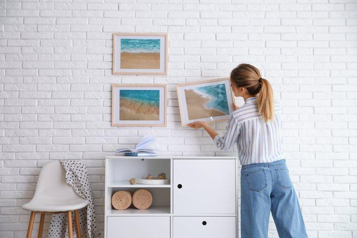 Woman hanging artwork
