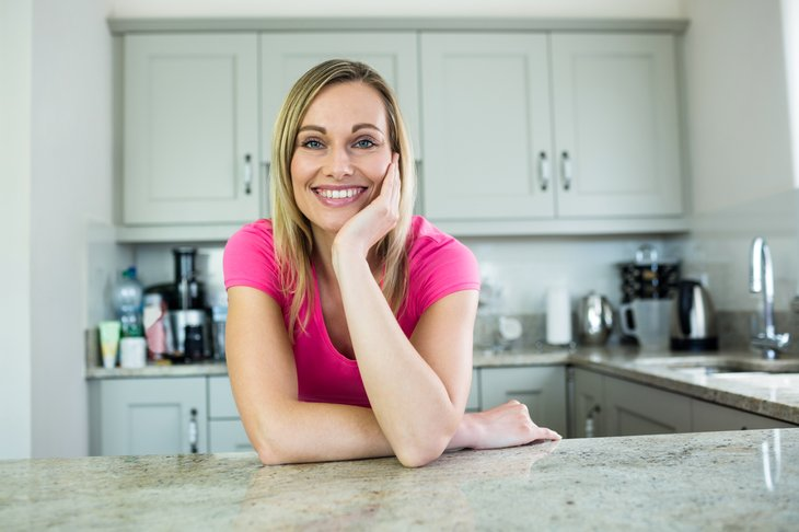 Woman in front of kitchen cabinets